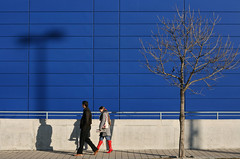 Red Boots (sonofsteppe) Tags: life street city blue winter shadow red urban woman man detail building tree men geometric lines horizontal architecture modern walking concrete 50mm daylight couple hungary exterior boots outdoor pavement candid bare budapest gray young explore human simplicity environment moment simple exploration fragment passersby sonofsteppe pusztafia zugl urbanlifeoftrees
