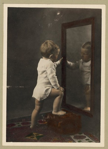 I sure am good looking in my pajamas ... Vintage Picture of a Cute Young Boy Looking at His Reflection in the Mirror