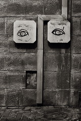 Ever get the feeling you're being watched? (Gilad Benari) Tags: street city urban bw art texture strange wall sepia print poster nose israel telaviv eyes funny raw drain sidewalk 5d  markii florentin       giladbenari   homur  homurous