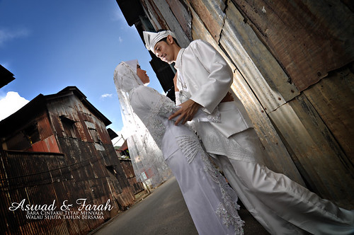Aswad & Farah, poses in front of a rusted zink wall in Sungai Lembing. Shot by tom ramzul