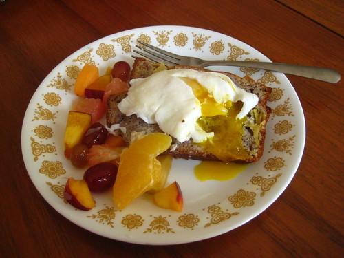 poached egg over banana bread with fruit salad