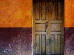 high school colors / light on a door to the past (msdonnalee) Tags: door sunlight puerta doors  entrance explore porta portal tr entry  purpleandgold woodendoor colourartaward donnacleveland plainbrowndoor faintraysoflight closeddoortothepast photosbydonnacleveland