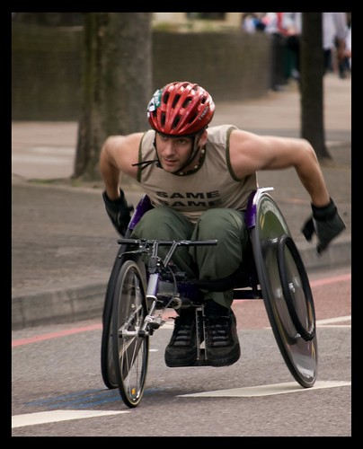 A wheelchair user competing in a marathon, caught in the act of leaning forward for more power.