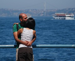 In Love. (Let Ideas Compete) Tags: bridge hairy woman man water ferry turkey boat hugging hug kissing couple barco barcos arms affection bokeh bald istanbul romance hips romantic had brunette galata sleeveless viewfromabridge takenonabridge galeta takenfromabridge viewonabridge