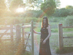 Let me in (Gareth Smith) Tags: trees woman sun grass lady forest fence 50mm haze woods gate dress romantic brunette f18 blackdress project365 olympuse600