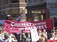 foule en marche, sur la rue St-Joseph au bord de la biblio. Gabrielle-Roy sous une bannière: Charest contre les pauvres