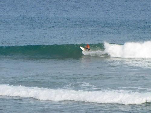 bald dude catches a wave