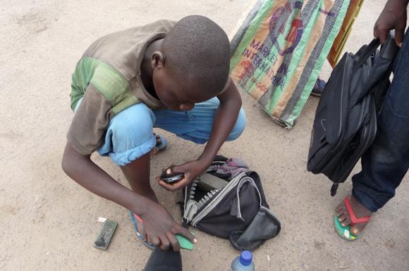 Un cireur de chaussures dans une rue de Kinshasa