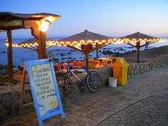 dahab menu (kexi) Tags: blue sea sky water bicycle menu lights restaurant evening nikon december dahab redsea egypt coolpix umbrellas 2008 kartpostal thebestofday