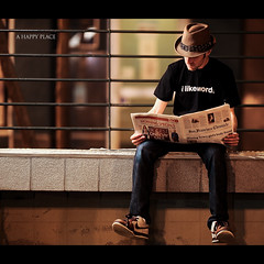 Day Ninety Eight (Dustin Diaz) Tags: sanfrancisco city selfportrait me hat wednesday reading newspaper words downtown dof bokeh humor nike 365 potrait civiccenter literacy toomuchwork featured project365 dustindiaz strobist dustindiazcom moltn ilikewords dedfolio