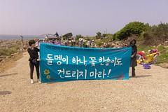 Choi Sung Hee拉著抗議布條,布條上寫著:不要碰這裡的一顆石頭,一朵花!