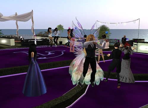 Description: Two couples dancing in the foreground with a third woman watching. In the background are several more couples and individuals. They appear to be dancing outside, and you can see the sea in the distance.