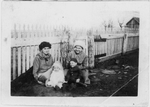 Two women and two babies at the fence