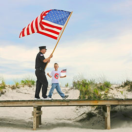 4th of July boardwalk parade led by Fireman and son in Davis Park, Fire Island