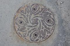 Manhole cover with Coast Salish tadpoles, Vancouver (ouno design) Tags: vancouver design cover tadpoles manhole bacteria douglascoupland coastsalish jenweih susanpoint kellycannell