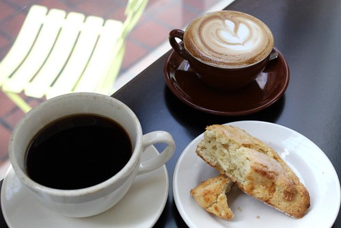 A pour-over drip coffee, a cappuccino, and a lemon-ginger scone
