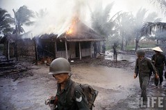 S. Vietnamese infantrymen warily moving past hut they set ablaze after they found it held communist literature during Vietnam War. 1962 par VIETNAM History in Pictures (1962-1963)