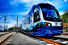 All Aboard the Seattle Link Light Rail (Surrealize) Tags: seattle new blue trees sky white reflection green public clouds train nikon shiny rocks perspective tracks rail sunny transportation masstransit washingtonstate hdr gravel soundtransit 9exp linklightrail d700 surrealize