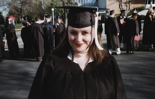 A woman posing in her graduation gown outdoors