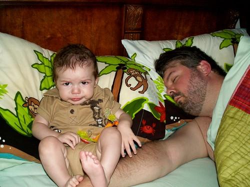 Finn makes a face next to his sleeping father