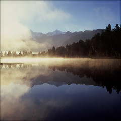Blue Gold (AndrewNZ) Tags: morning blue trees newzealand sunlight mist lake mountains reflection topf25 topv111 wow golden topf50 topv555 topv333 glare fuji topv444 topv222 hasselblad 500c topv777 southernalps topv666 aotearoa lakematheson mountcook aoraki velvia50 mounttasman tewaipounamu interestingness142 interestingness71 i500 explore20feb09