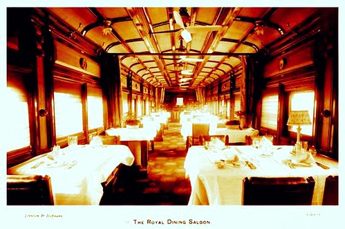 A view of the interior of the carriage containing the Royal dining saloon showing a number of tables laid out with crockery, cutlery and glasses