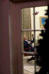 President Barack Obama tosses a football in the Oval Office.