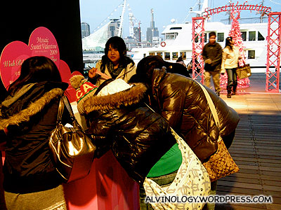 Japanese teens excitedly writing their wishes on free red ribbons