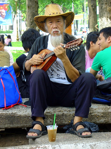 Friendly man playing Mandolin in the park near Notre Dame Cathedral, Ho Chi Minh City, Vietnam