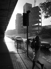 Northern Baptism (Pete Boyd) Tags: street uk england people blackandwhite bw baby cars wet rain underpass manchester child traffic candid father roundabout streetphotography overpass queue jam unposed hulme soaked spontaneous pedestriancrossing sliproad mancunianway