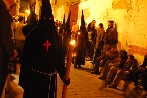 semana santa sevilla. Semana Santa - Seville, Spain - The weeklong religious processions continue through the narrow alleys of Seville during the evening of Good Friday.