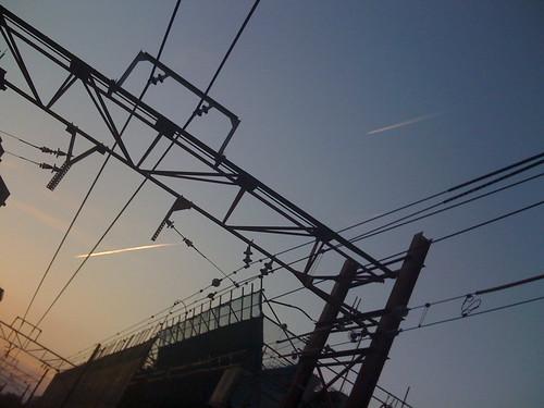 夕暮れの踏み切りと飛行機雲2