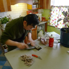 Knife sharpening (Thirteen Of Clubs) Tags: me kitchen square crop bathrobe whetstone waterstone carbonsteel squarish knifesharpening croppedsquare eyeloupe lx3 curveadjustment chineseknife dmclx3 jewelersloupe roundedcleaver japanesewaterstone 10xjewelersloupe