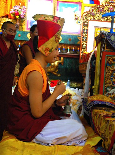 Young Sakya Prince wearing the Sashu hat - Lama HE Avikritar Rinpoche praying with dorje and bell, behind him, monks who are master of ceremonies, Tharlam Monastery, Bodha, Kathmandu, Nepal by Wonderlane