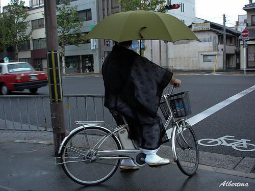 Montando en bici eléctrica con paraguas y kimono