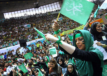 Another photo of protesters in Iran, this photo having been taken from the ground. People dressed in green, waving green flags, and wearing green headbands, make their voices heard.