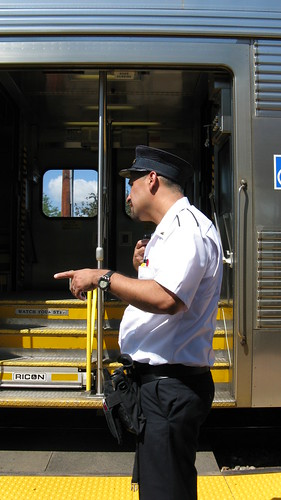 Metra commuter train conductor talking to the locomotive engineer via two way radio. Northbrook Illinois. June 2009.
