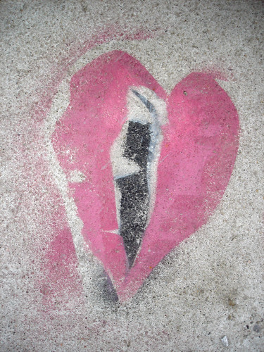 graffiti on concrete: red-pink heart with a black streak down the center --