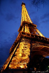 La Tour Eiffel (Hylda_H) Tags: city travel blue urban paris france beauty night outdoors photography gold lights iron europe flickr fotografie eiffeltower illumination lookingup advertisement latoureiffel frankrijk bizarre parijs lacit beautyisintheeyeofthebeholder skywardbound excapture hyldah