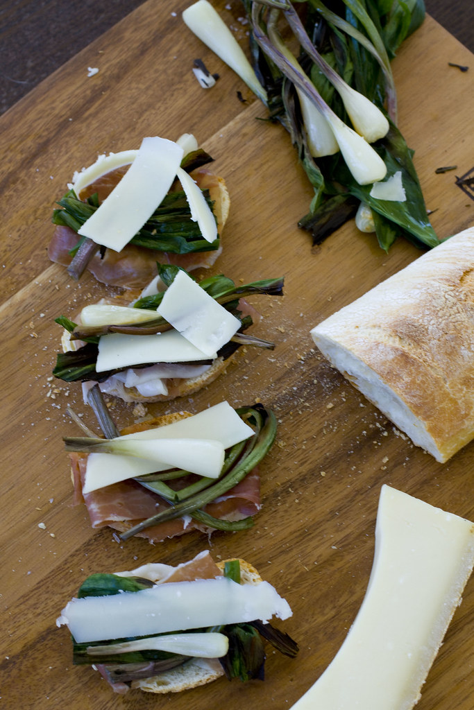 Prosciutto, ramps, and gruyere on wood board