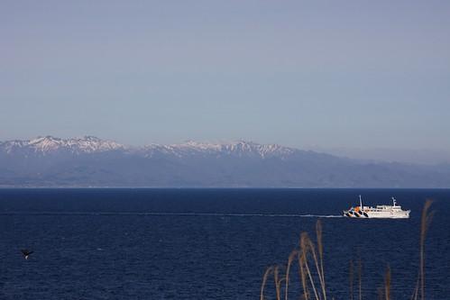 遊楽部岳が見下ろす海をフェリーが進む