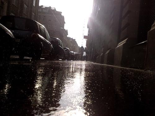 Regen auf Gehsteig bei Gegenlicht