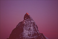 when night turns to day (Ron Layters) Tags: pink red orange mountain sunrise geotagged dawn switzerland glow purple pentax slide velvia transparency zermatt matterhorn grainy fujichrome wallis alpenglow valais 1k cervin pentaxmz10 cervino eastface mountainsalps elevation40004500m altitude4478m summitmatterhorn montcervin 4478m mattertal colouredsky ronlayters slidefilmthenscanned 14692ft horu butitwasverydark summitblockearlymorning geo:lat=45977341 geo:lon=765996