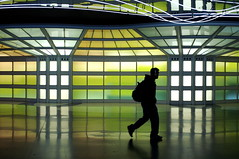 (Greg Adams Photography) Tags: travel light chicago man reflection colors lines silhouette underground lights colorful neon squares geometry shapes corridor tunnel terminal traveller adventure transit backpack headphones ord chicagoohare 2007 unitedairlines spselection hhsc2000