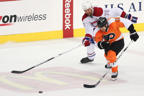 Hal Gill #75 of the Montreal Canadiens and Arron Asham #45 of the Philadelphia Flyers race towards the loose puck