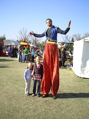 The girls with a man on stilts