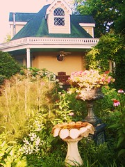 back of the yellow and green rose cottage with flowers in the garden and a cement bird bath