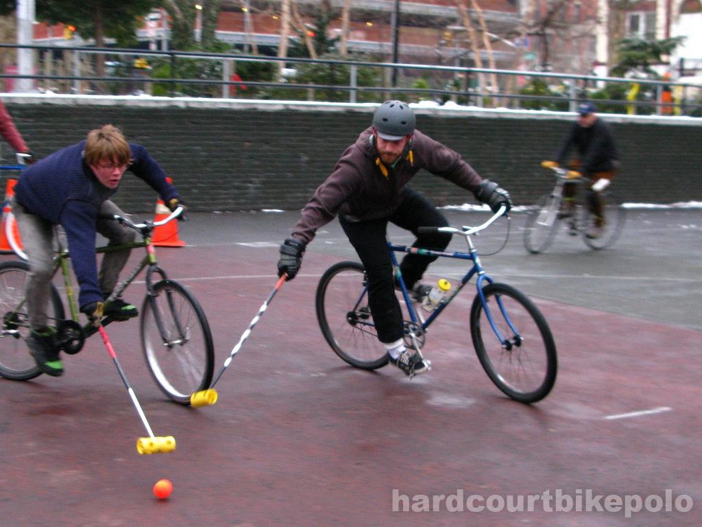 Hardcourt Bike Polo Lief and Paul reaching for ball