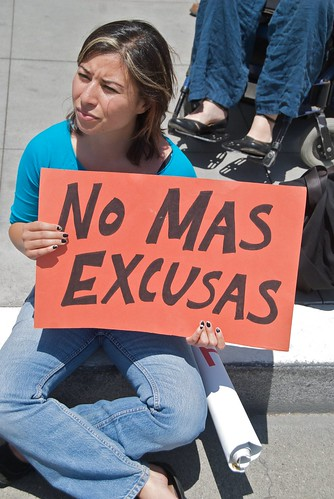 A person seated on a sidewalk holding up an orange sign reading 'no mas excusas.' A wheelchair user is seated behind the person, with only the wheelchair user's legs and feet in the frame.