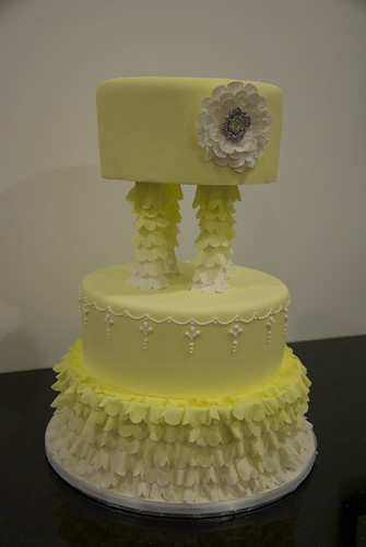 A frilly yellow and white wedding cake adorned with an edible sparkling